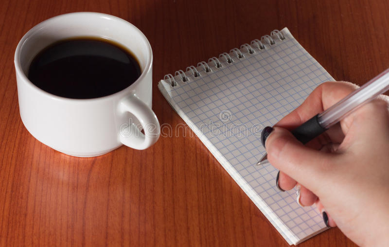 Coffee and notebook. Coffee break, you can manage to make the necessary entries royalty free stock photography