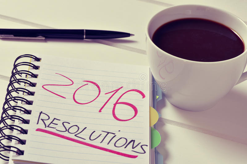 Coffee and notepad with the text 2016 resolutions. Closeup of a notebook with the text 2016 resolutions written in it and a cup of coffee on a white table stock photo