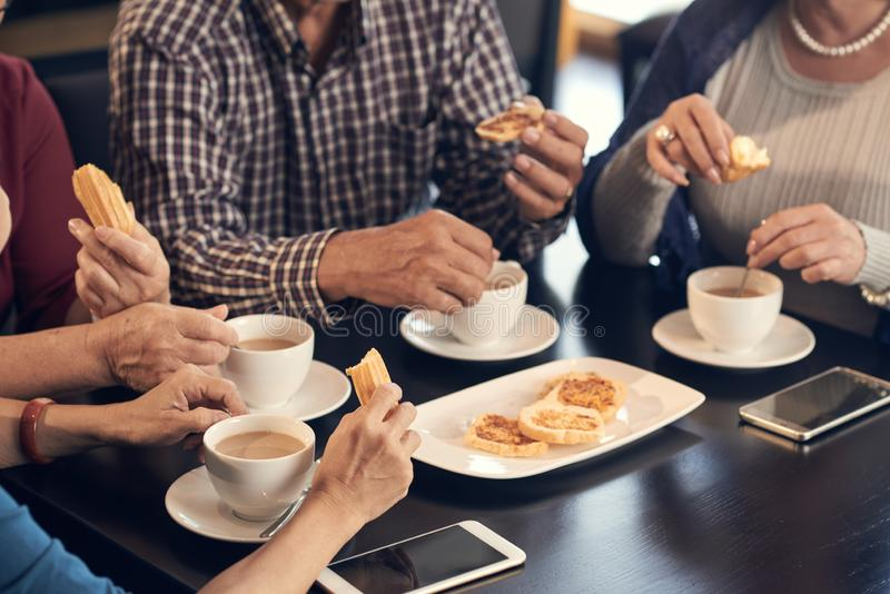 Coffee with old friends. Cropped image of seniors having coffee and cookies for breakfast stock photo