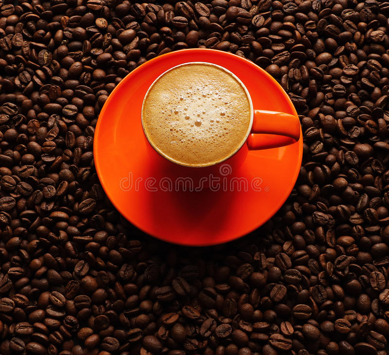 Coffee in orange cup on saucer with coffee beans. Coffee in orange cup on saucer with dark coffee beans background royalty free stock photography