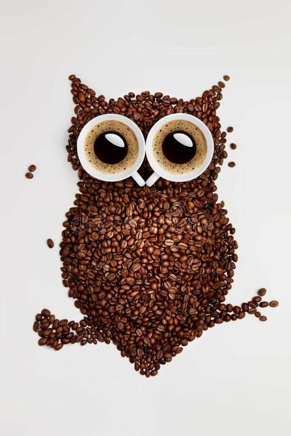 Coffee owl. A funny owl made of roasted coffee beans and two cups stock photos