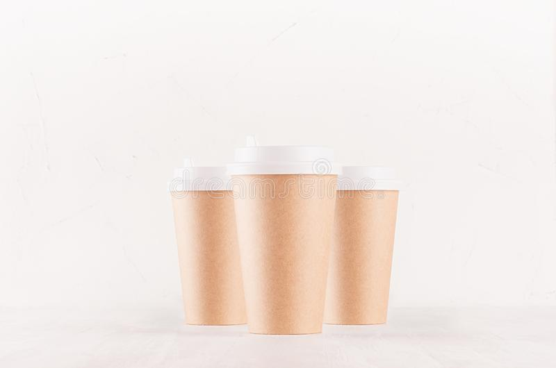 Coffee packing mockup - group kraft brown paper cups with white cap closeup on white wood board, coffee shop interior. stock image