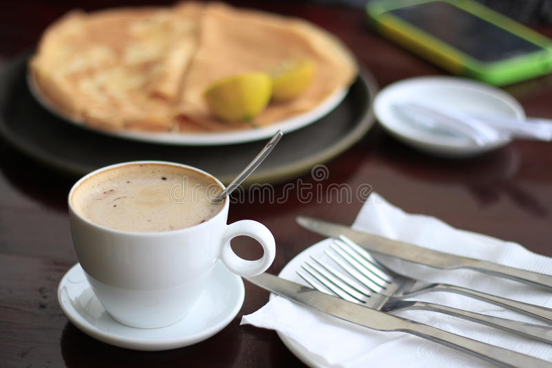 Coffee with pancak. Lemon on pancakes white coffeee royalty free stock photography