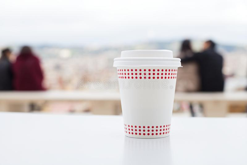 Coffee with panoramic view. Capuccino in a white paper cup on a table - coffee terrace with panoramic view stock image