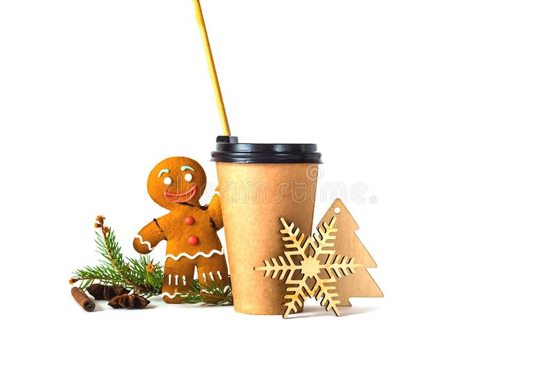 Coffee in paper cup with wooden straw and a gingerbread man on white background with Christmas decorations. The concept of the holiday. Closeup. Copy space royalty free stock image
