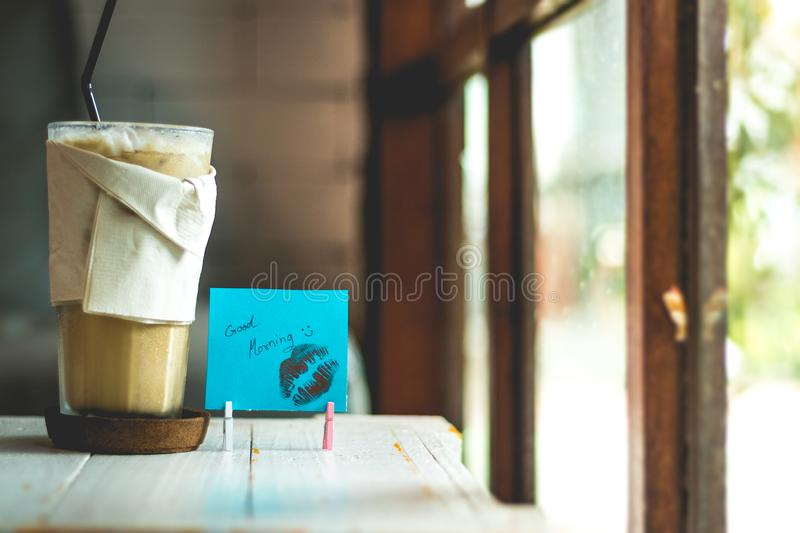 Coffee and paper note with good morning. On a table stock photo