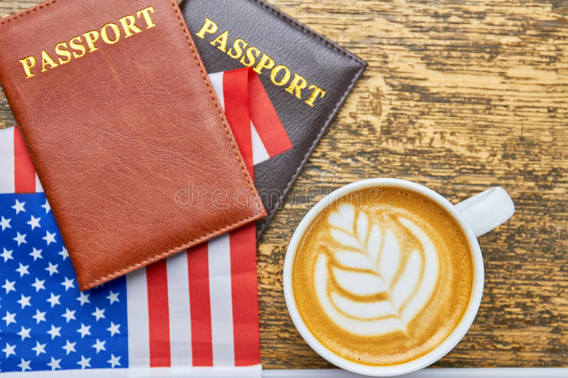 Coffee, passports and US flag. White latte cup top view. American citizenship requirements royalty free stock images