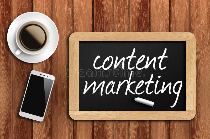 Coffee, phone and chalkboard with content marketing words.  stock image