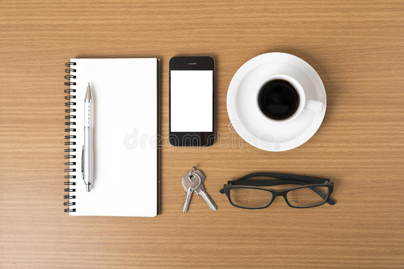 Coffee,phone,notepad,eyeglasses and key. On wood table background royalty free stock images