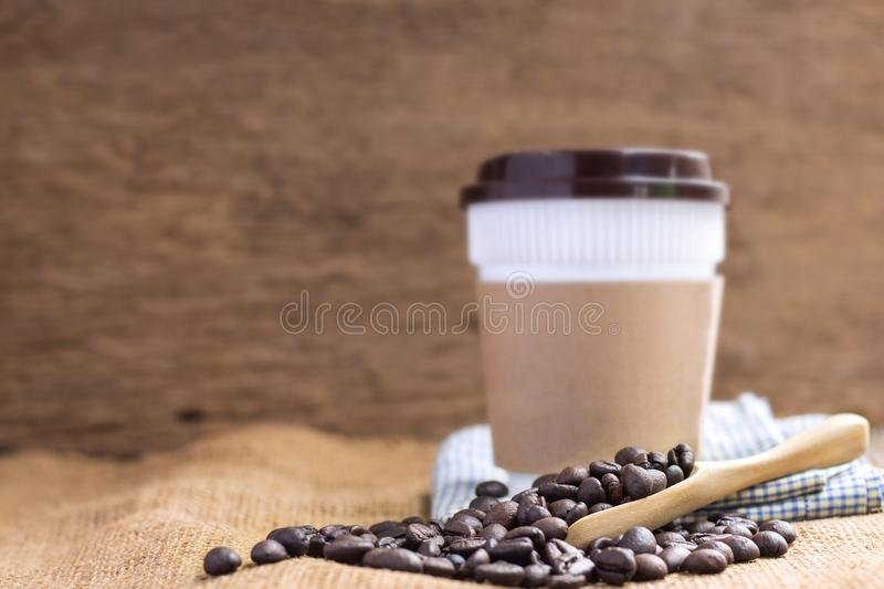 Coffee plastic cup with cardboard sleeve and a pile of coffee be stock images