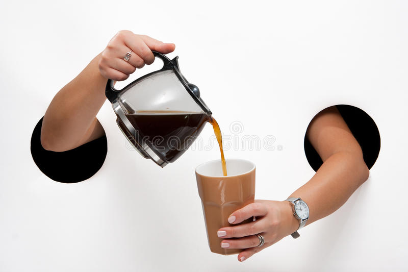 Coffee pot. Female hands through the holes on a white background pour coffee from coffee pot into a cup stock images