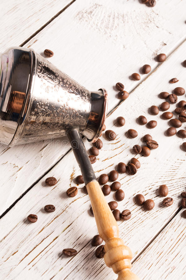 Coffee pot and scattered coffee. Beans on the table royalty free stock images