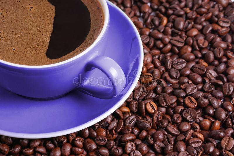 Coffee in purple cup on table surrounded with coffee beans.  royalty free stock photography