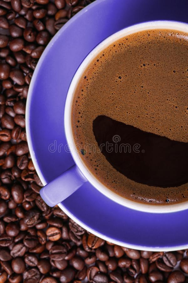 Coffee in purple cup on table surrounded with coffee beans.  royalty free stock photos