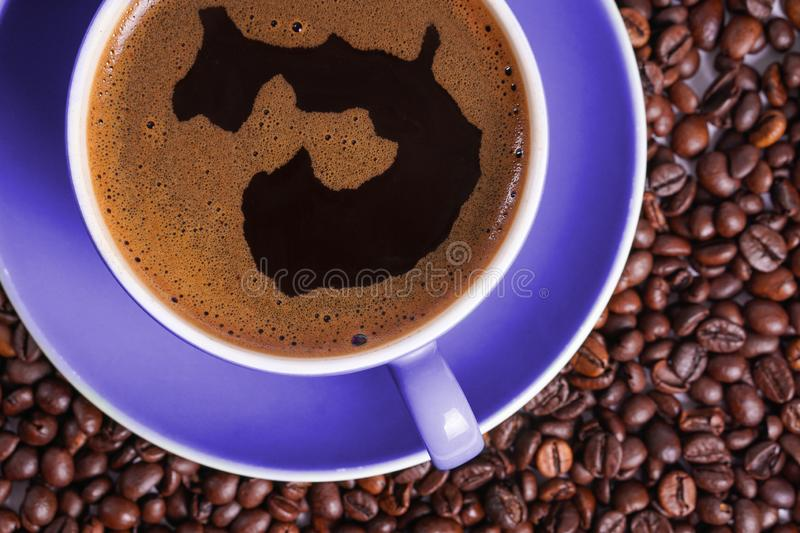 Coffee in purple cup on table surrounded with coffee beans.  royalty free stock photo