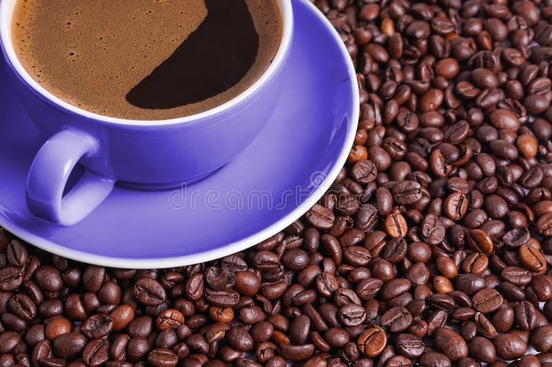Coffee in purple cup on table surrounded with coffee beans.  stock images