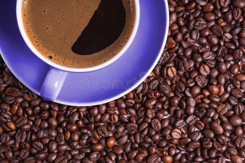 Coffee in purple cup on table surrounded with coffee beans.  stock photography