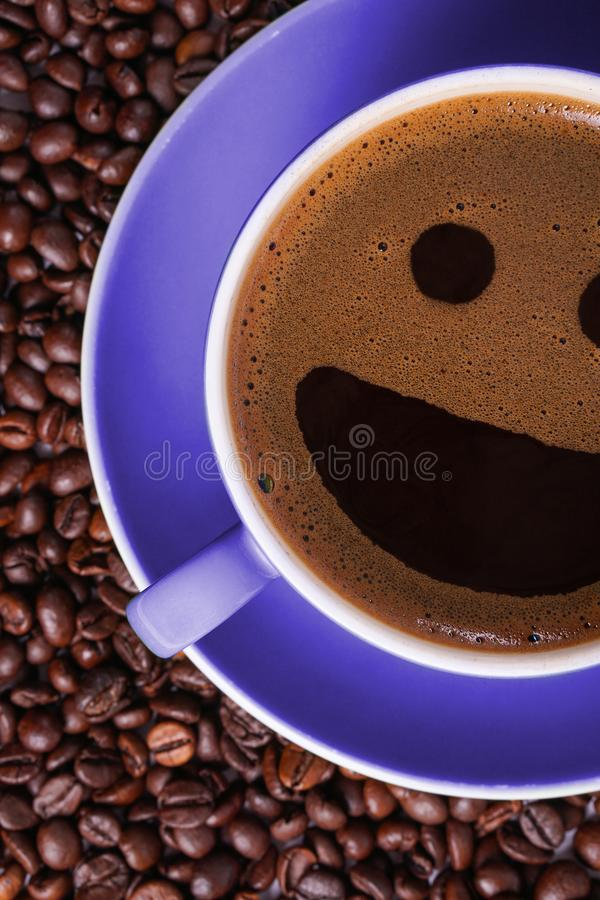 Coffee in purple cup on table surrounded with coffee beans. Coffee in shape of smile stock photo