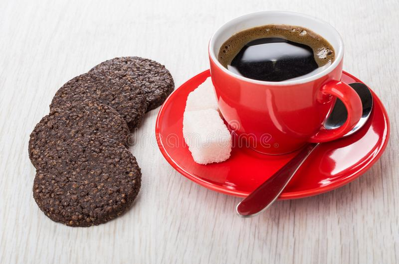 Coffee in red cup, chocolate cookies with airy rice. Coffee in red cup on saucer, chocolate cookies with airy rice on wooden table stock photos