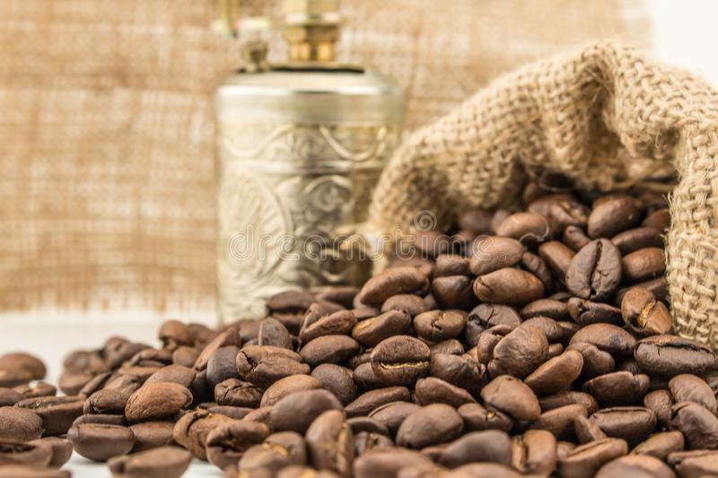 Coffee beans get out of the bag and gold grinder. stock images