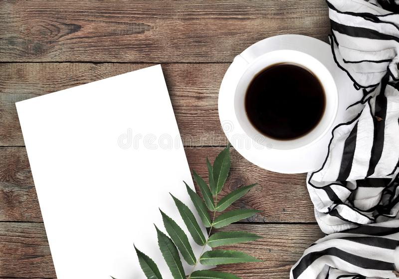 Coffee, scarf, empty paper blank and leaf on wooden background. royalty free stock photography