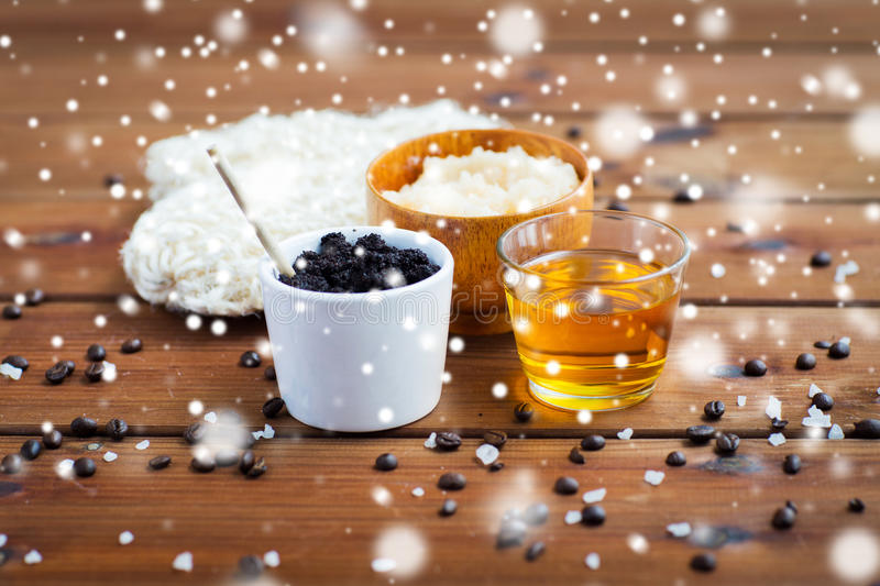 Coffee scrub in cup and honey on wood. Beauty, spa, bodycare, bath and natural cosmetics concept - coffee scrub in cup and honey on wooden table over snow royalty free stock image