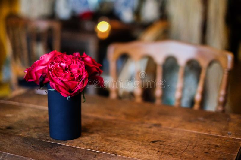 In coffee shop cafe, the red rose flower in black vase on the table for background or texture - vintage concept royalty free stock photo