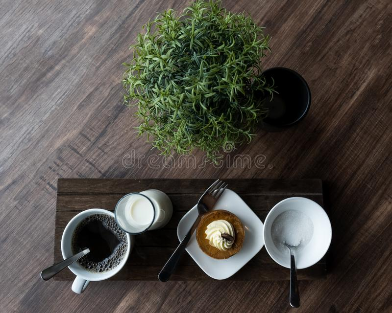 Coffee Shop Edibles. Table top view of coffee, milk, cheesecake, and sugar. Use for titles, backgrounds, small business stock photography