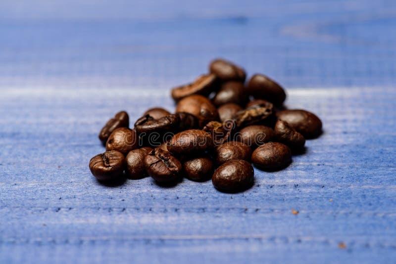 Coffee shop eller lager Nytt grillat kaffeslut upp Högbönor på blå träbakgrund Grad av att grilla kaffe arkivfoto