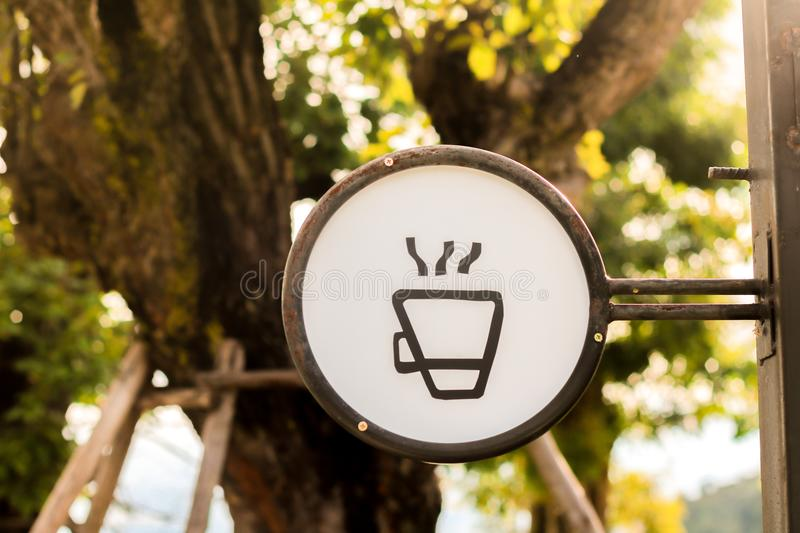 Coffee shop sign. Coffee cup hot outside shop sign steaming wall white urban info town icon small message illuminated downtown house emblem beverage glowing royalty free stock photos