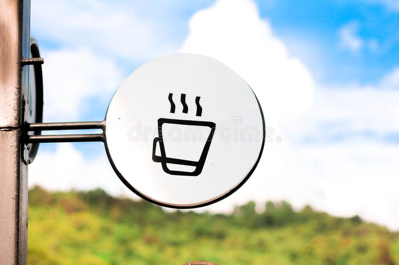 Coffee shop sign. Coffee cup hot outside shop sign steaming wall white urban info town icon small message illuminated downtown house emblem beverage glowing royalty free stock photo