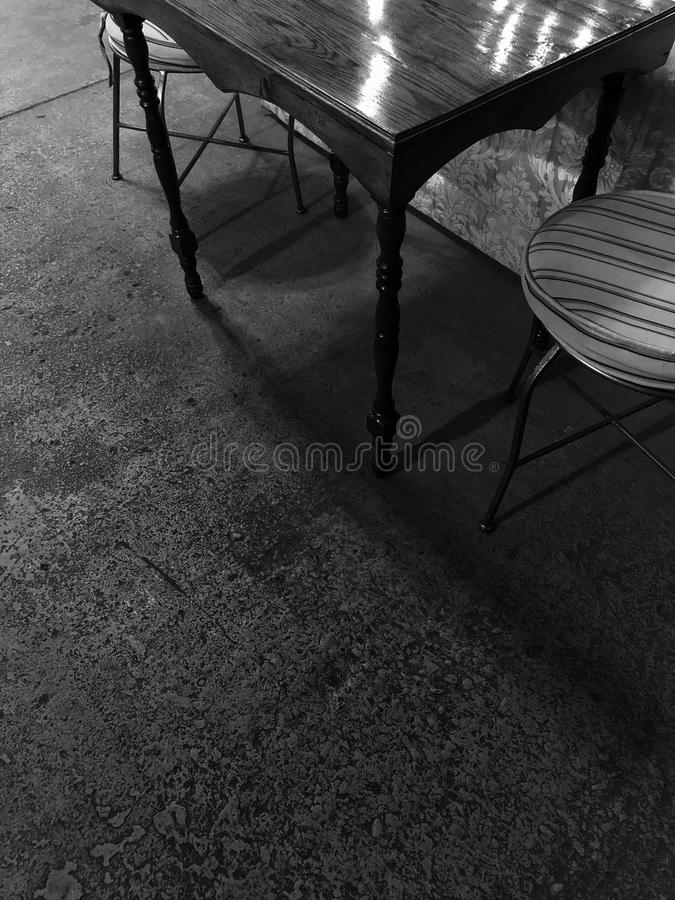 Coffee Shop table and chairs. Vintage style table and chairs in a coffee shop opened within a vintage mill factory. black and white and color profiles at a high stock images