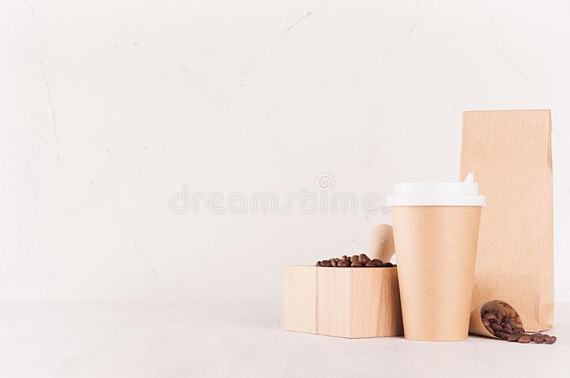 Coffee shop template for branding identity - brown paper cup, packet, mortar with coffee beans on white wood board, copy space. Coffee shop template for royalty free stock photography