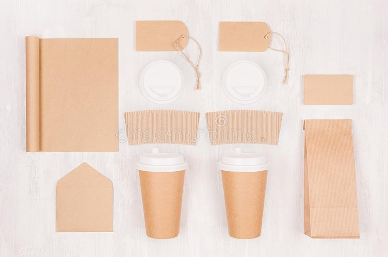 Coffee shop template for branding identity - two brown paper cups with blank notebook, packet, label, card, cap, envelope on wood. stock photo