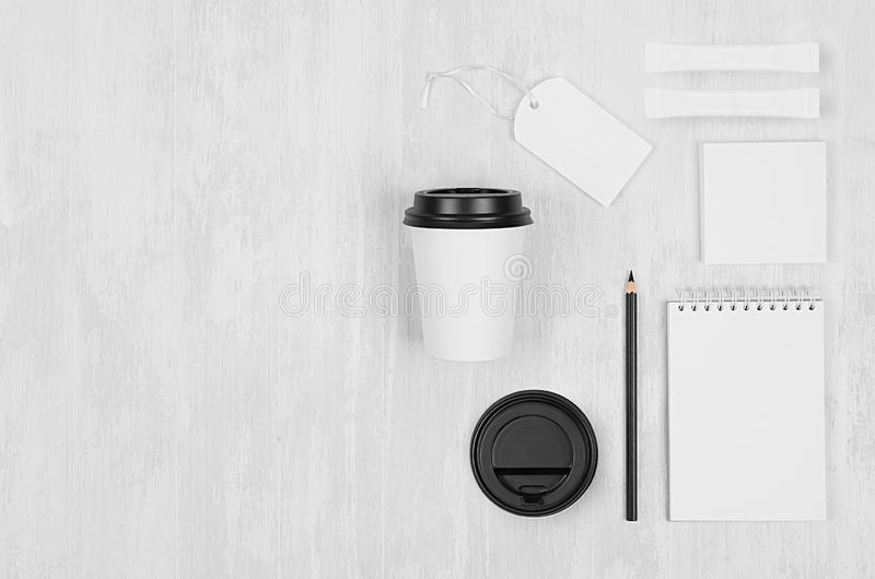 Coffee shop template for branding identity - white paper cup, black cap, blank notebook, label, card on white wood board. stock image