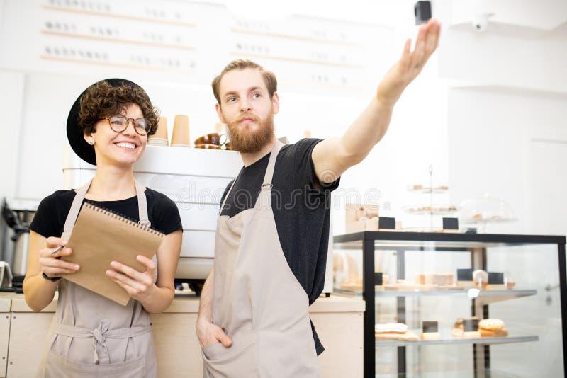 Coffee shopchef som förklarar uppgifter till den unga servitrins royaltyfri foto