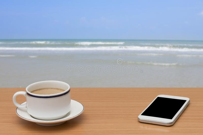 Coffee and smart phone on wooden table with tropical sea and beach.  stock photo