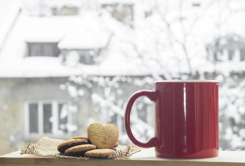 Coffee in the snow. Red cup of coffee on a beautiful snow winter background royalty free stock photo