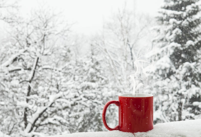 Coffee in the snow. Red cup of coffee on a beautiful snow winter background stock photo