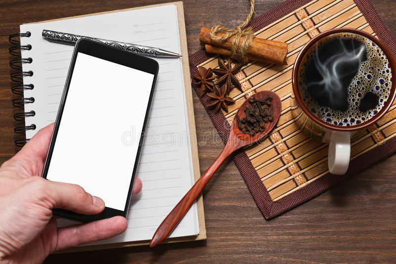 Coffee with spices, diary and a cell phone in hand stock photo