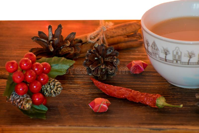 Coffee, spices and pine cones on a wooden background. Christmas concept. A cup of hot coffee with milk, cinnamon and chili on a wo stock photo