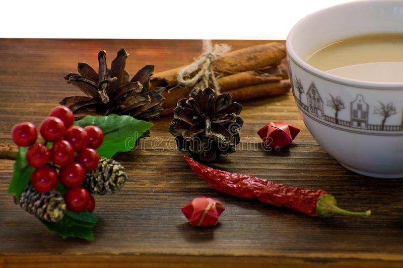 Coffee, spices and pine cones on a wooden background. Christmas concept. A cup of hot coffee with milk, cinnamon and chili on a wo royalty free stock image