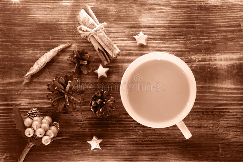 Coffee, spices and pine cones on a wooden background. Christmas concept. A cup of hot coffee with milk, cinnamon and chili on a wo royalty free stock photo