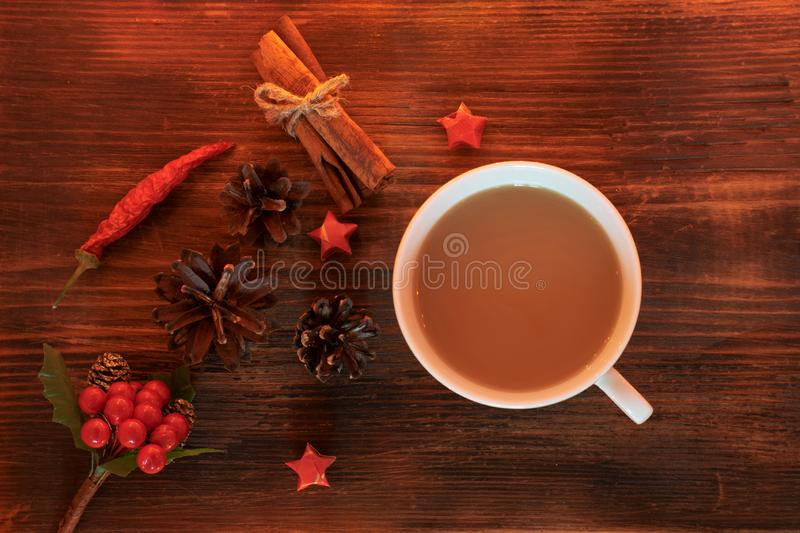 Coffee, spices and pine cones on a wooden background. Christmas concept. A cup of hot coffee with milk, cinnamon and chili on a wo royalty free stock photography