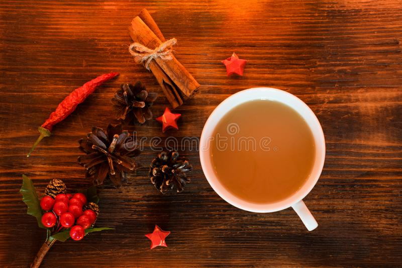 Coffee, spices and pine cones on a wooden background. Christmas concept. A cup of hot coffee with milk, cinnamon and chili on a wo royalty free stock photos