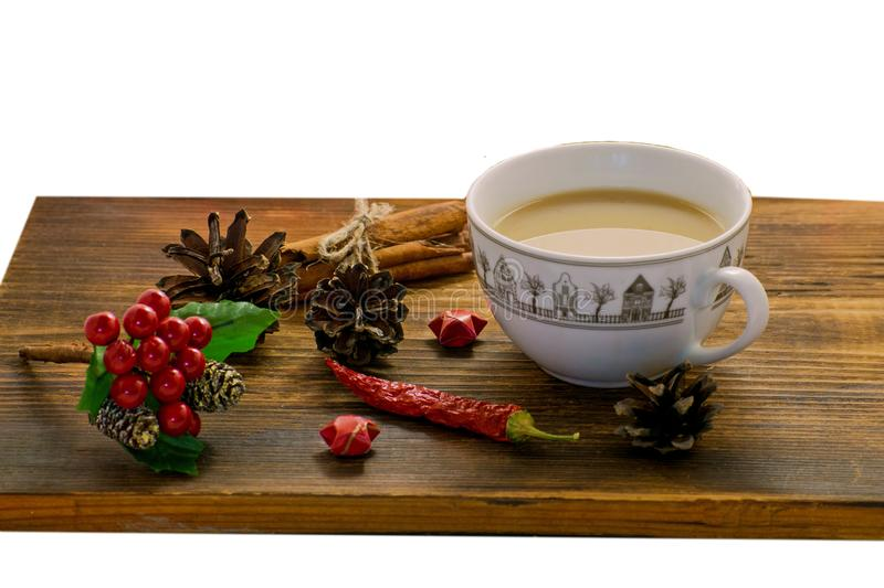 Coffee, spices and pine cones on a wooden background. Christmas concept. A cup of hot coffee with milk, cinnamon and chili on a wo stock image