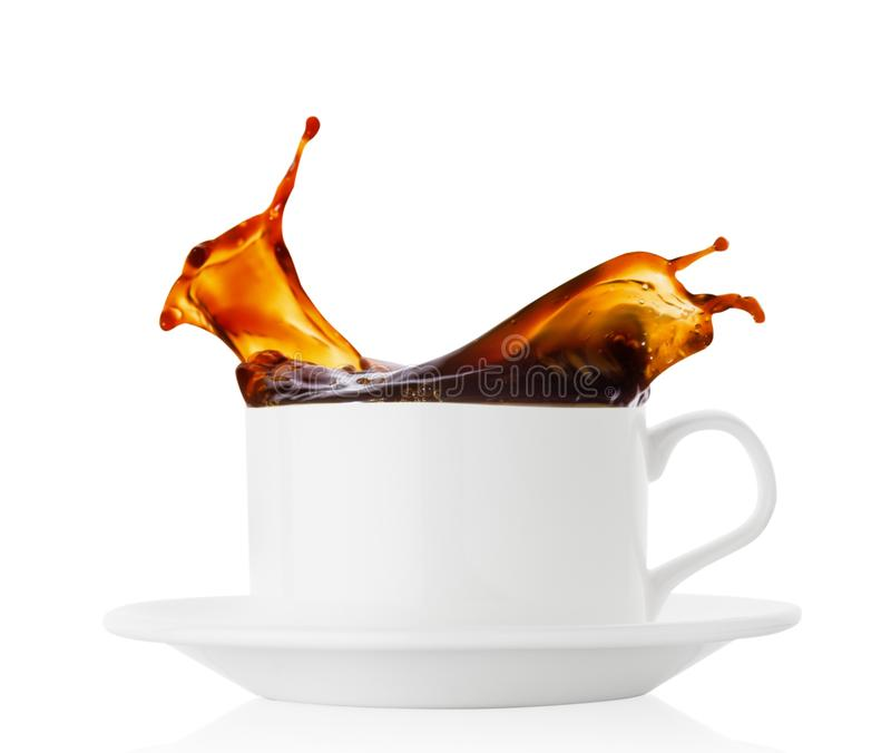 Coffee splash in a white cup with saucer royalty free stock photography