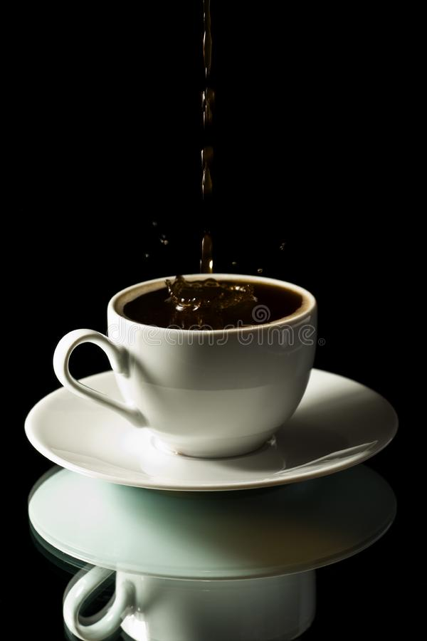 Coffee splashing into white cup stock photo