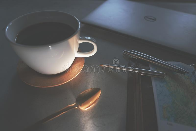 Coffee, spoon, laptop travel map and pens on concrete table at evening stock photo