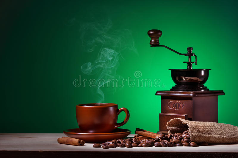 Coffee with steam coffee grinder and coffee beans. On a green background royalty free stock photography